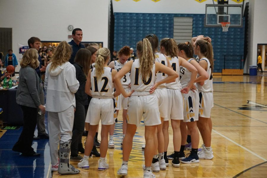 The girls basketball team huddles up on a timeout.