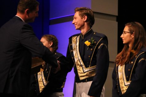 Trumpet leader Carson Bretz shakes band director Iain Novoselich's hand at the
