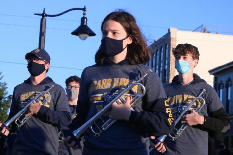 The trumpet section of the marching band stands at attention while marching in downtown Grand Haven.