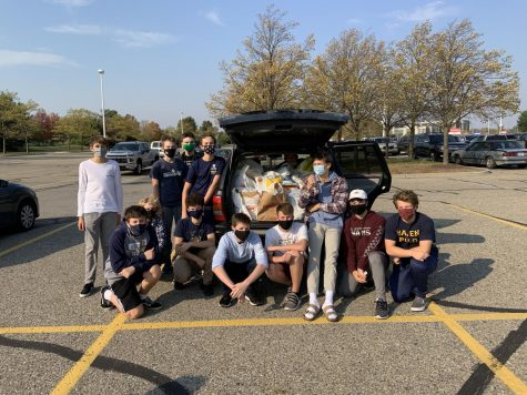 FOOD DRIVE: Members of the team pose in front of their haul after successfully completing their shopping. The trip was a quick one, due to the fact they had so many helping hands.