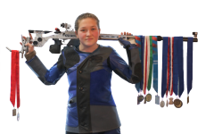 MEDALS: Adrianna supports one of her rifles on her shoulders while showing off many of her medals. Over the course of her career she has collected even more than what is shown but they couldn't all fit on the gun.