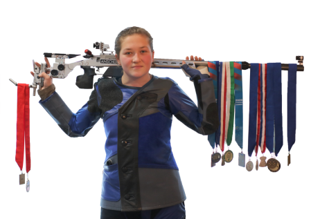 MEDALS: Adrianna supports one of her rifles on her shoulders while showing off many of her medals. Over the course of her career she has collected even more than what is shown but they couldn