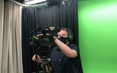 FILMING: Senior Zachary Whitaker peers through the lens of a GHTV video camera in the studio.