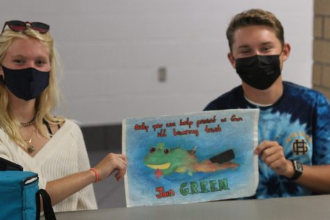 Sophomores Payden Pittman and  Mackenzie Stanhope hold up Green club sign, promoting the club during the club mixer at lunch on September 2nd.(Photo taken by Megan Voorhees)